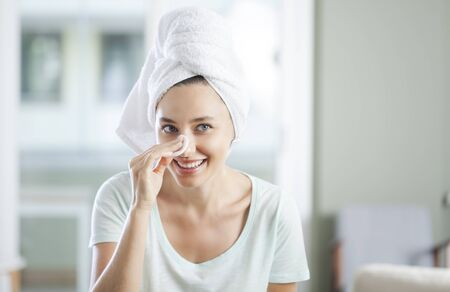 Beautiful young woman touching her face with sponge and smiling while standing in front of the mirror 版權商用圖片
