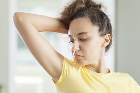 Young woman who sniffs armpits and her face is negative in bathroom