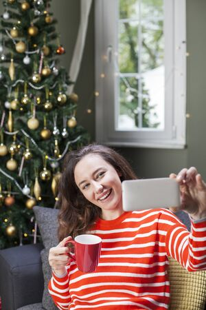 Happy young woman taking selfie over christmas tree sit on her sofa Standard-Bild - 135007749