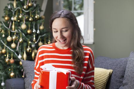 Woman in front of Christmas tree holding present Standard-Bild - 135007751