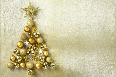 Christmas tree made of bauble decoration, gold background Standard-Bild - 135007752