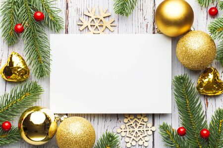 Christmas tree branches, blank paper with decoration on white plank Standard-Bild - 135007762