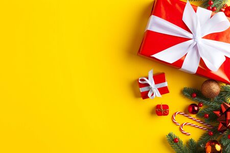 Christmas decoration on yellow background. Red gift box with christmas ornament. Top view. Standard-Bild - 135007922