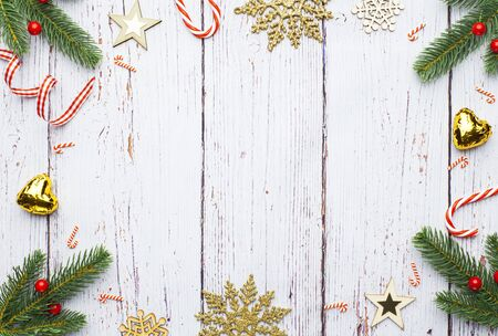 Christmas frame made of fir branches, red berries on white plank. Christmas wallpaper. Standard-Bild - 135007924