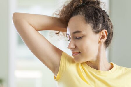 Young woman smelling her underarms in her livingroom at home Standard-Bild - 135007572