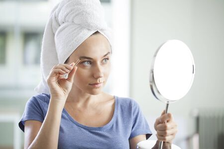 Young woman shaping her eyebrows with tweezer, looking in mirror at home Standard-Bild - 135007628