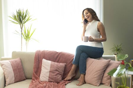 Young woman calling talking on the phone at home, cheerful teen girl enjoys pleasant mobile conversation, smiling female holding phone making call by telephone in living room Standard-Bild - 135007658