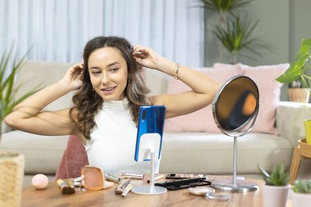 Famous blogger. Cheerful female vlogger recording with smart phone and showing cosmetics products while recording video and giving advices for her beauty blog. Standard-Bild - 135007666