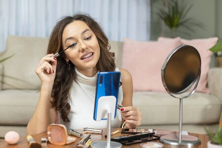 Famous blogger. Cheerful female vlogger recording with smart phone and showing cosmetics products while recording video and giving advices for her beauty blog. Standard-Bild - 135007667