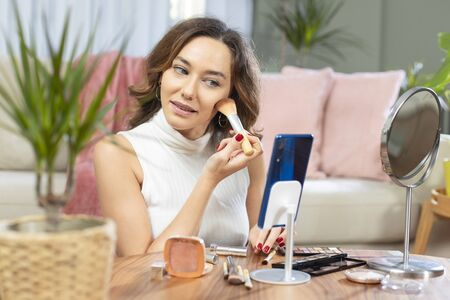 Famous blogger. Cheerful female vlogger recording with smart phone and showing cosmetics products while recording video and giving advices for her beauty blog. Standard-Bild - 135007668