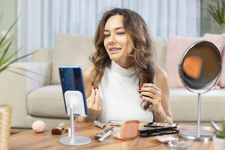 Famous blogger. Cheerful female vlogger recording with smart phone and showing cosmetics products while recording video and giving advices for her beauty blog. Standard-Bild - 135007670