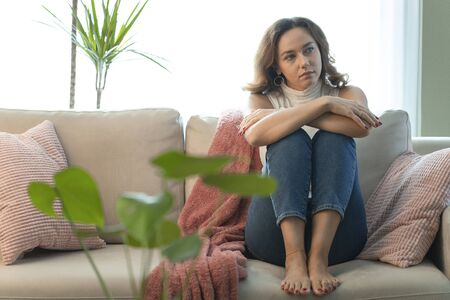 Frustrated confused female feels unhappy problem in personal life. Upset woman looking away sitting on sofa at home.