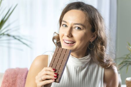 Young woman holding a chocolate bar to enjoy the taste and are dieting, healthy eating, feeling temptation. Smiling young woman eating chocolate.