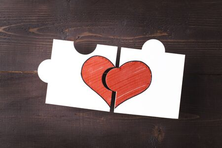 Two pieces of a puzzle forming a heart on a wooden background 写真素材