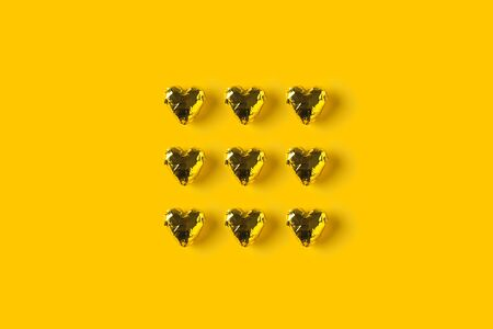 Gold colored heart chocolates on yellow background