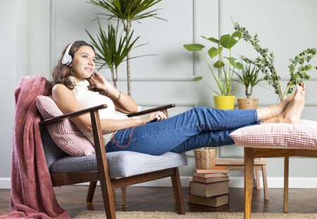 Full length shot of an attractive woman with headphone sitting on armchair and listing to music.
