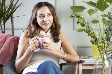 Young woman sit down on armchair drinking coffee. Leisure activity, lifestyle for people concept.
