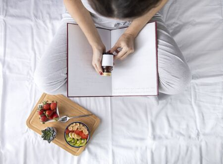 Young woman eating healthy breakfast in bed, while holding a vitamin bottle in his hand. Top view on bed