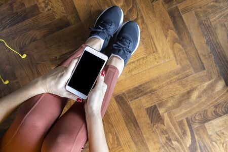 Young  has a rest after the exercise in home holds the smartphone sitting on floor. Mock-up include Banco de Imagens