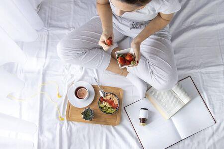 Young woman eating healthy breakfast in bed. She eaten from a fully bowl cornflakes and fruit. Top view on bed