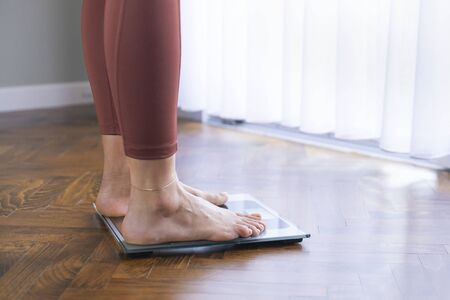 Young woman's feet on a scale. Diet and healthy living concept.