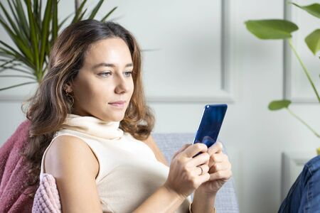 Young woman using a mobile phone while relaxing on the armchair at home