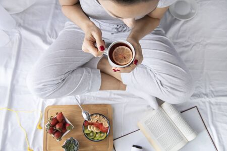 Young woman eating healthy breakfast in bed. She drinking herbal tea. Top view on bed