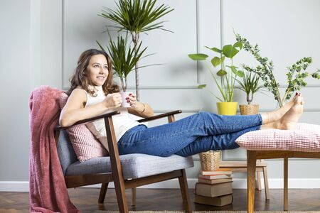 Full length shot of an attractive woman drinking coffee at home, sitting on armchair