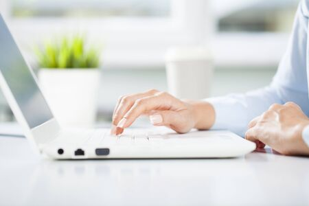 Businesswoman working on laptop pc at office. Corporate workplace image, close-up Standard-Bild