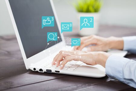 Female hands using laptop with icon social media and social network