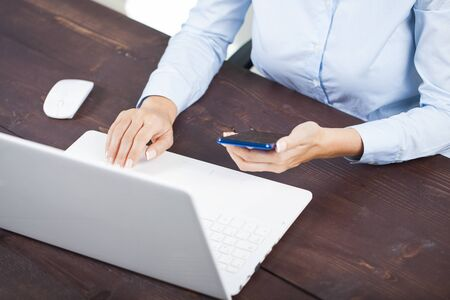 Cropped shot of a business woman using smart phone and notebook laptop computer. Standard-Bild