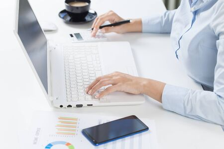 Businesswoman using calculator and laptop for matching financial data saving at office. Business financial, tax, accounting concept. Banco de Imagens