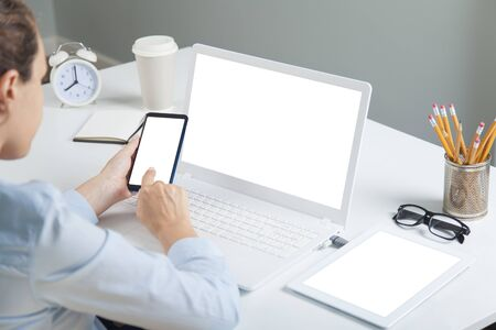 Woman holding a white screen smartphone and blank white screen laptop computer on a desk. Template for your designs easy editable Banco de Imagens