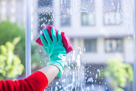 Hands in gloves with cleaning cloth wipes window. Washing the glass on the windows with cleaning spray. Window cleaning at home. Foto de archivo