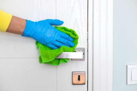 Woman cleaning a door handle with a disinfectant rag Foto de archivo