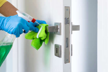 Woman cleaning a door handle with a disinfecting spray Foto de archivo