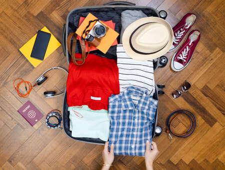 Woman preparing summer luggage. Travel suitcase prepareing concept