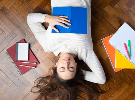 Relaxed young woman lying on the floor and surrounded by books. Exam period for high school students Foto de archivo