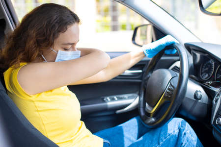 Young woman with face mask sneezing into elbow in the car