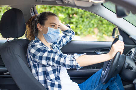Young woman in a mask sitting in a car, protective mask against , driver on a city street during a outbreak.