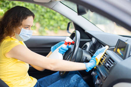 Woman in the car with protective glove and facial mask. Hands with blue gloves. She sprinkling disinfectant and cleaning the car. Foto de archivo
