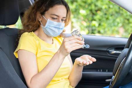 Young woman using hand sanitizer while sitting in car Foto de archivo