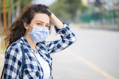 Young woman on the street wearing face protective mask to prevent
