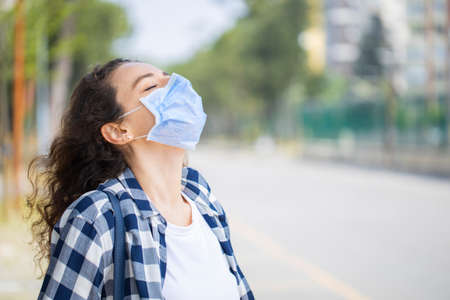 Young woman breathing fresh air on the street wearing medical mask