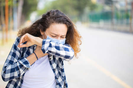 Woman with face mask sneezing into elbow while walking in the street