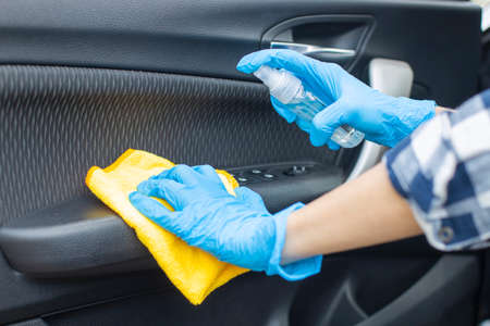 Woman's hand wearing protective gloves cleaning car door handle with hand sanitizer Foto de archivo