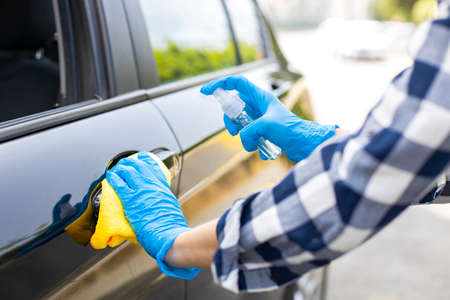 Woman's hand wearing gloves and spraying disinfectant car door handle