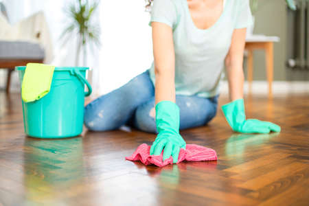 Young housewife with gloves cleaning the floor. Routine house chores concept