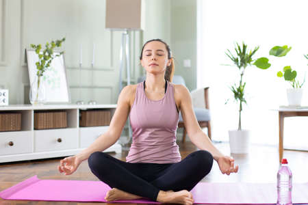 Young woman with closed eyes practicing yoga in lotus position in living room