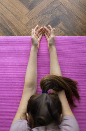 Sporty young woman practicing yoga in living room